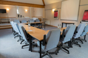 Conference meeting with desks and chairs with projector screen in Garden conference room at Guyers House Hotel