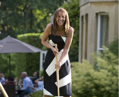 Lady holding croquet club in gardens of Guyers House Hotel