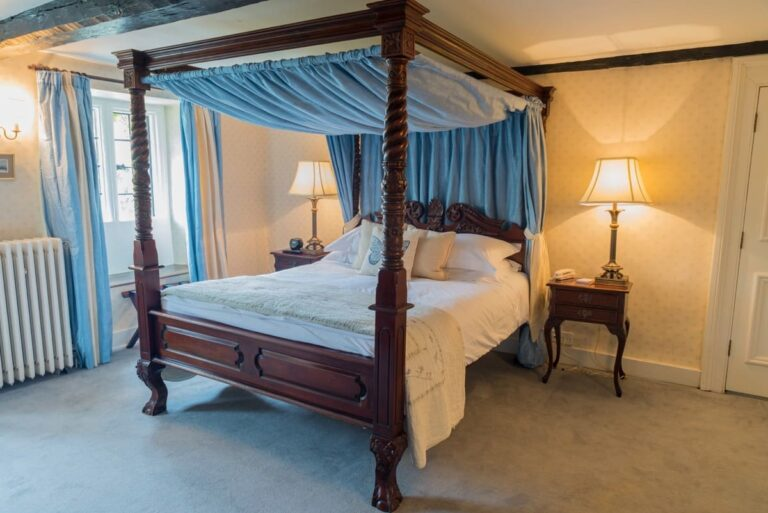 Double bedroom with four-poster bed and soft furnishings at Guyers House Hotel
