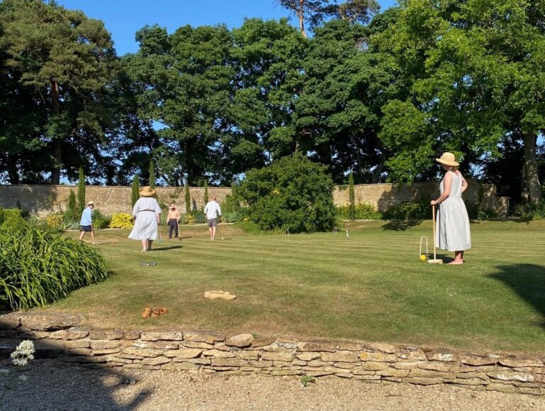 People playing croquet on the lawn in barefeet