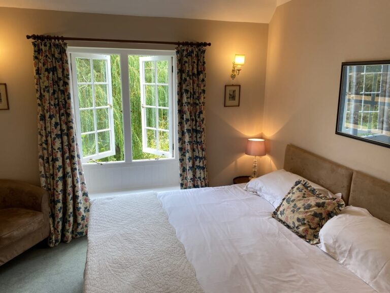 Double bedroom with soft furnishings and view into garden at Guyers House Hotel