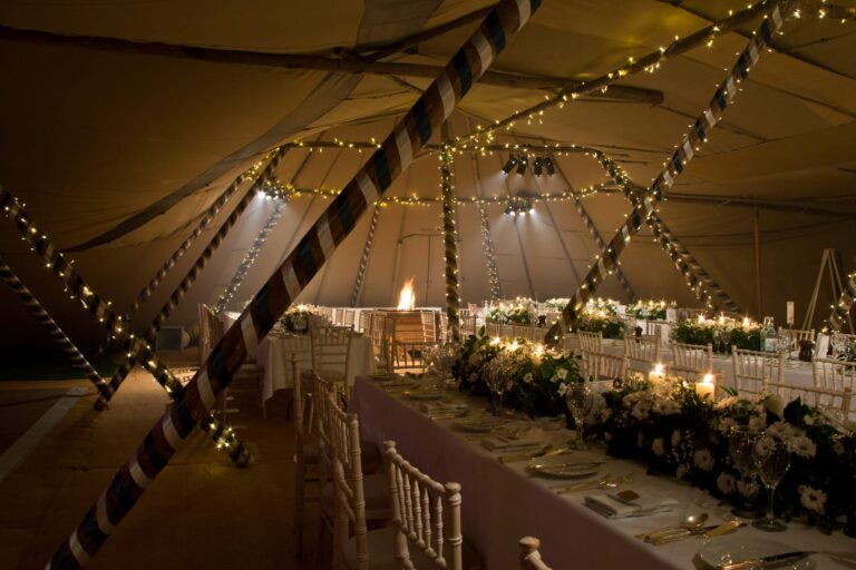 Inside wedding marquee with fair lights and fire pit
